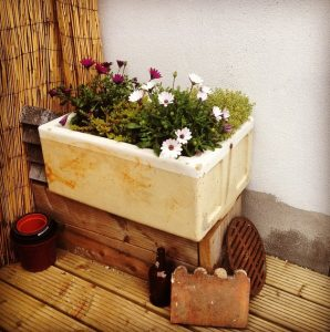 upcycled containers in a city garden